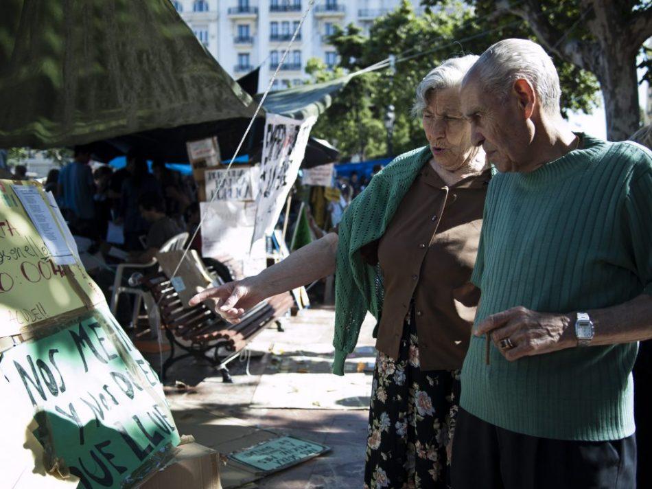 Una pareja visita #acampadavalencia y comenta alguno de los carteles reivindicativos.
