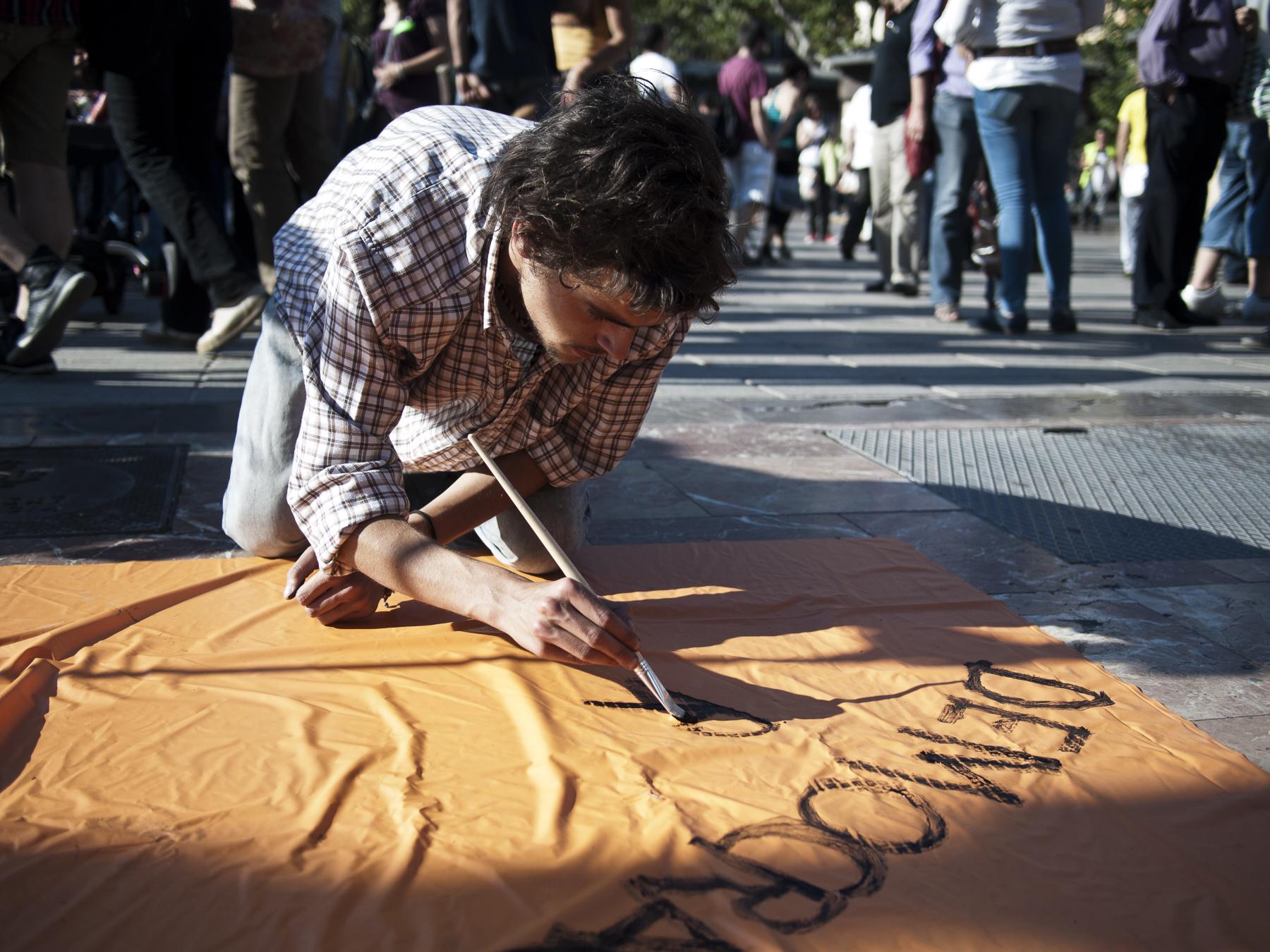 """Un joven escribe una pancarta pidiendo """"democracia real"""" en #acampadavalencia"""