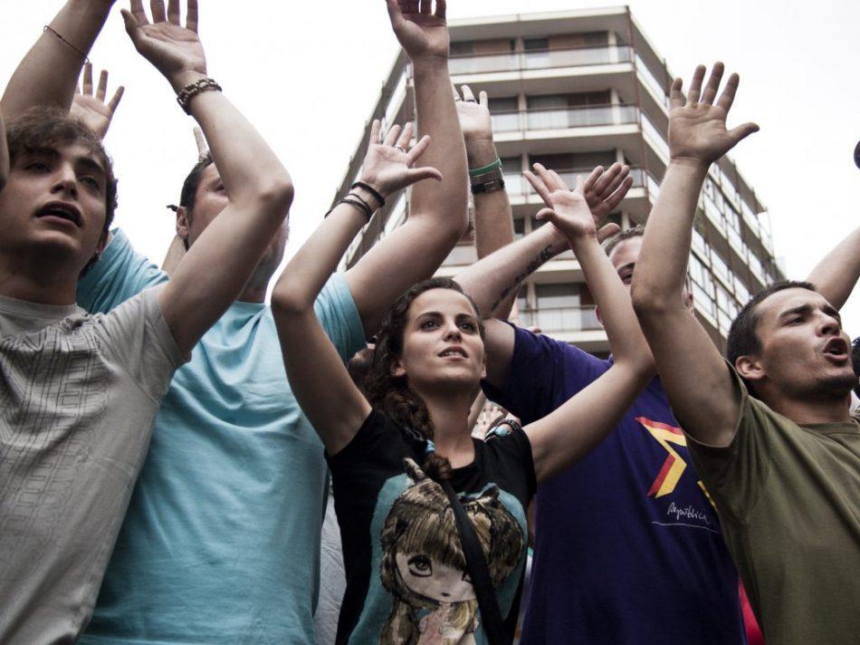 Los manifestantes muestras su pacifismo a los efectivos de policía que controlavan la concentración y manifestación en solidaridad con los desalojadas en Barcelona que tuvo lugar en Valencia.