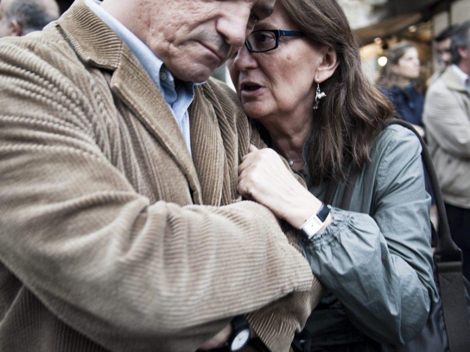 Una pareja hablan al oido durante una asamblea.