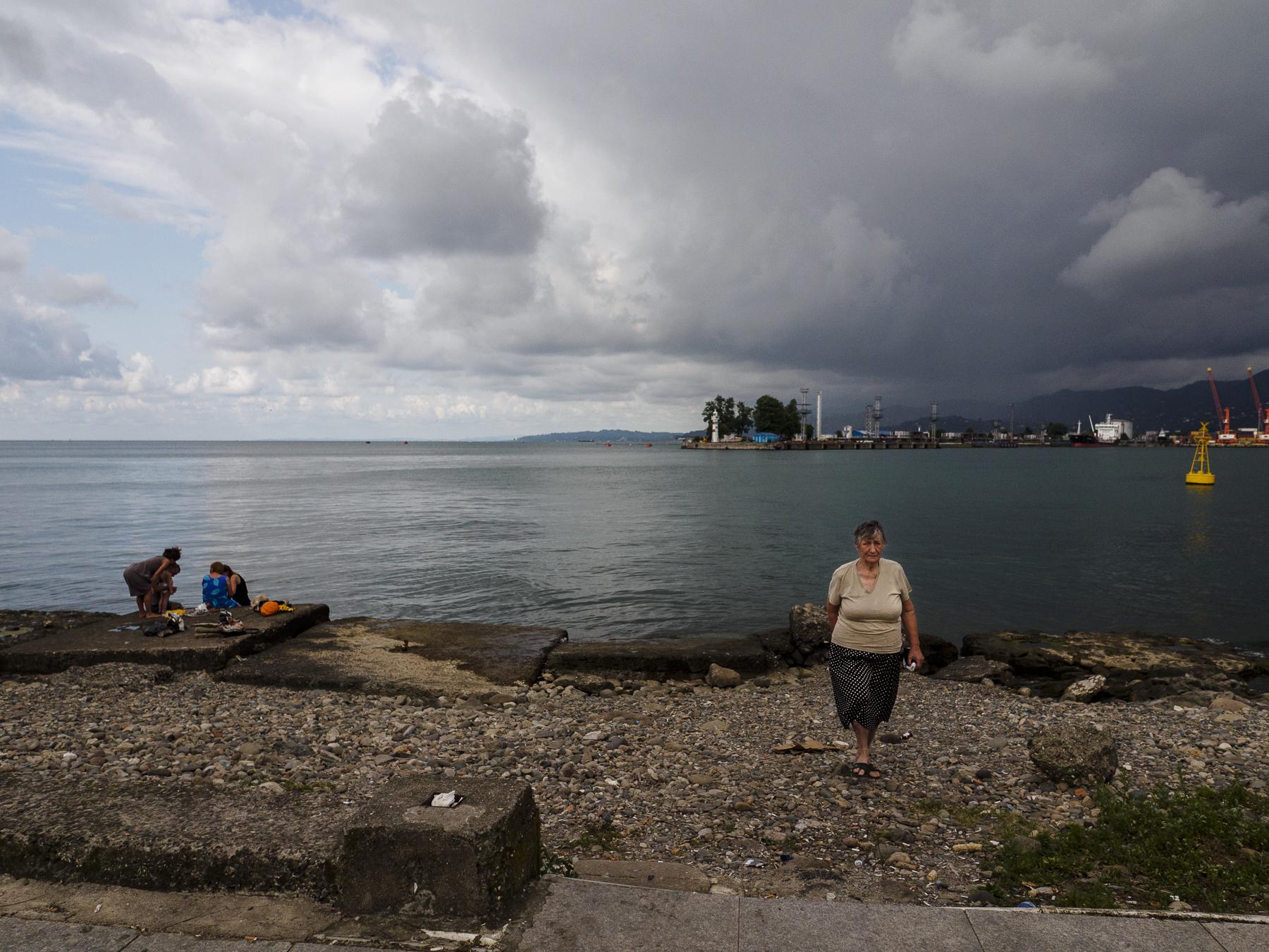 Una familia pasa el día en la playa junto al puerto de Batumi